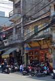 Vietnam - Hanoi - Typical street scene the Old Quarter - Hang Quat Street - religious embroideries, men and scooters. Vietnam - Hanoi - Typical street scene from Royalty Free Stock Image