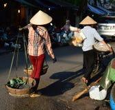Vietnam - Hanoi - typische straatscène van het Oude Kwart - dames in koelies die voedsel in het District van Hoan verkopen Kiem stock fotografie