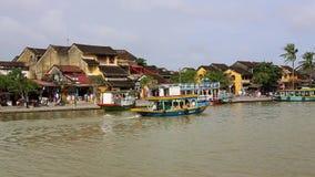 Vietnam Hoi An - Januari 2017: Fl?ten f?r n?jefartyg p? Bon River mot bakgrunden av hus p? stranden lager videofilmer