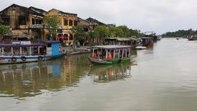 Vietnam Hoi An - Januari 2017: Fl?ten f?r n?jefartyg p? Bon River mot bakgrunden av hus p? stranden arkivfilmer