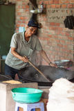 Vietnam, Mekong Delta-December 10, 2013. Man makes rice popcorn. Rice popcorn is made in coconut candy factory which is located in Tien Giang Province near to Royalty Free Stock Photos