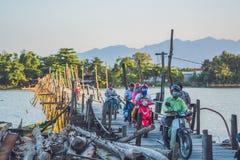 Vietnam, Nha Trang - April 10, 2017: Old wooden bridge and Vietnamese motorcyclists Royalty Free Stock Images