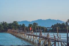 Vietnam, Nha Trang - 10 de abril de 2017: Puente de madera viejo y motoristas vietnamitas Imagen de archivo libre de regalías