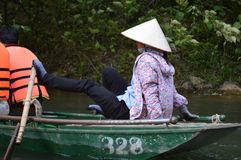 Vietnam - North - Trang An - traditional lady rower in conical hat rowing with her feet. Vietnam - northern province of Ninh binh - Trang an landscape scenic Royalty Free Stock Photo