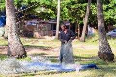 VIETNAM, PHU QUOC - 5 DE NOVIEMBRE DE 2014: Pescador tradicional que repara sus redes de pesca en la playa el 5 de noviembre de 2 Fotos de archivo