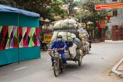 Vietnam Traffic a Full Load. A man bikes his way through the streets of Hanoi Vietnam with a full load on November 16, 2013 Stock Photos