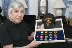 Vietnam vet show his medals earned during service. Vietnam veteran Franky Gonzalez holds some of his earned medals Stock Photography