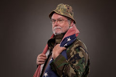 Vietnam Veteran with American flag. Smiling Vietnam Veteran with American flag around his neck stock image