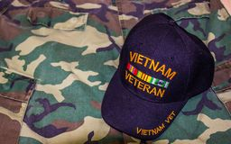 Vietnam Veteran Hat On Camouflage Uniform. Vietnam Veteran Ball Cap On Top Of Jungle Green Camouflage Uniform Stock Photos
