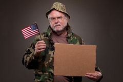 Vietnam Veteran holding a cardboard piece and American flag. Vietnam veteran dressed in camouflage, holding a cardboard piece and American flag stock image