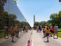 Vietnam veteran som är minnes- med turister och Washington Monument i bakgrund arkivbild