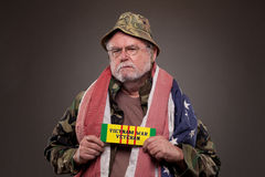 Vietnam Veteran with  war tag. Vietnam Veteran with American flag around his neck, holding a tag Royalty Free Stock Image