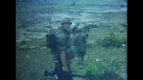 Vietnam War - US marching in Vietnam. Vietnam War Color. Some US soldiers walk in Vietnam on a meadow and look around stock footage
