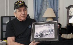 Vietnam war veteran holds an old war photo of himself. stock photo