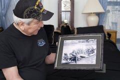 Vietnam war veteran looks at old war photo of himself. Royalty Free Stock Photo