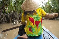 Vietnam woman with a paddle in boat, Mekong River Stock Image