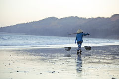 Vietnam woman in vietnamese hat walking on seacost Royalty Free Stock Photo