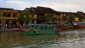 Vietname, Hoi An - em janeiro de 2017: Flutuadores do barco de prazer em Bon River contra o contexto das casas na margem vídeos de arquivo
