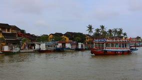 Vietname, Hoi An - em janeiro de 2017: Flutuadores do barco de prazer em Bon River contra o contexto das casas na margem video estoque