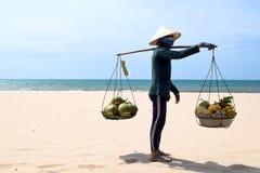 VIETNAME, Mui Ne - 27 DE MARÇO DE 2017 Vendedor do fruto da praia que anda na praia em Vietname Está vendendo cocos, bananas e o  imagens de stock royalty free