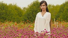 Vietnamees meisje met lang zwart haar die zich in een aanplantings purpere bloemen bevinden vietnam royalty-vrije stock afbeeldingen