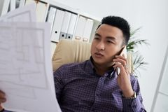 Engineer consulting client. Vietnamese architect consulting client on the phone Royalty Free Stock Images
