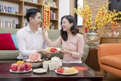 Vietnamese couple holding good luck item for new year. Vietnamese asian couple wear red to celebrate chinese new year smiling with the ang bao and hangings Stock Photos