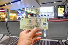 Vietnamese banknotes are in the hands of men on the airport background in Hanoi, Vietnam stock image