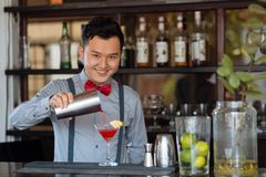 Vietnamese bartender. Smiling Vietnamese bartender making a cocktail at a bar counter Royalty Free Stock Photos