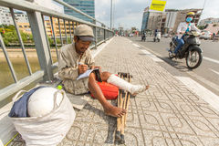Vietnamese beggar sitting on the street. Royalty Free Stock Photo