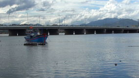 Vietnamese blue boat at anchor on the river. fishermen throwing fishing nets into the boat.in the background there is a bridge wi stock video