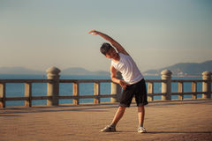 Vietnamese boy does bending aside on embankment at dawn Royalty Free Stock Photos