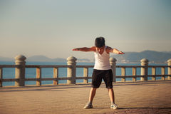Vietnamese boy does bending on embankment at dawn Royalty Free Stock Photography