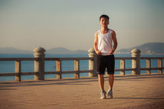 Vietnamese boy does exercises on embankment at dawn Royalty Free Stock Images
