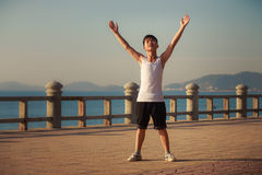 Vietnamese boy does exercises on embankment at dawn Royalty Free Stock Image