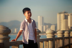 Vietnamese boy stands on sea embankment at dawn Royalty Free Stock Image