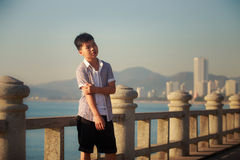 Vietnamese boy stands on sea embankment at dawn Stock Images