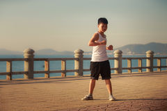 Vietnamese boy turns around on embankment at dawn Royalty Free Stock Photos