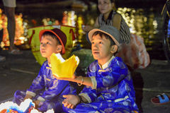 Vietnamese boys selling offerings, Hoi An, Vietnam. Hoi An, UNESCO World Heritage Site in Vietnam, july 2014. Two boys are selling candles in a basket to let Royalty Free Stock Photography