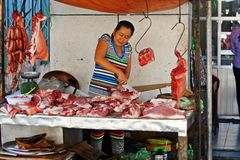 Vietnamese Butcher. A Vietnamese butcher cuts meat at a market stall in the Mekong Delta Stock Photography