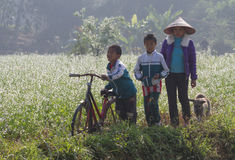 Vietnamese children going to school by bicycle. Moc Chau, Vietnam - Jan 10, 2016: Vietnamese children going to school by bicycle on a small grass country path Royalty Free Stock Images