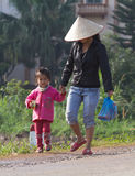 Vietnamese children going to school. Moc Chau, Vietnam - Jan 10, 2016: Vietnamese children going to school on a small grass country path among a field of cabbage Stock Images