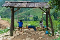 Vietnamese children playing on bamboo swing. Cat Cat, Vietnam - August 20, 2017: Vietnamese children playing on bamboo swing with mountain rice terraces on the Stock Photos