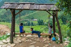 Vietnamese children playing on bamboo swing. Cat Cat, Vietnam - August 20, 2017: Vietnamese children playing on bamboo swing with mountain rice terraces on the Stock Photography