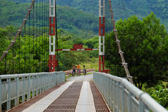 Vietnamese children ride bicycle on suspension bridge. LAM DONG, VIET NAM- JAN 1, 2017: Group of unidentified Vietnamese children ride bicycle cross suspension Royalty Free Stock Image