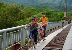 Vietnamese children ride bicycle on suspension bridge. LAM DONG, VIET NAM- JAN 1, 2017: Group of unidentified Vietnamese children ride bicycle cross suspension Stock Photo