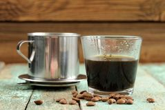 Vietnamese coffee brewed in French drip filter on turquoise wood Stock Image