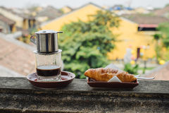 Vietnamese coffee and croissant on the table Stock Image
