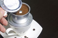 Vietnamese coffee maker is equipped on a cup. It is filled with ground coffee and pour boiling water. The man lifted the lid of th. E brewer Royalty Free Stock Images