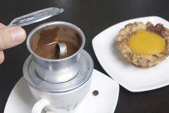 Vietnamese coffee maker is equipped on a cup. It is filled with ground coffee and pour boiling water. There is a cake on the sauce. R. The man lifted the lid of Stock Images